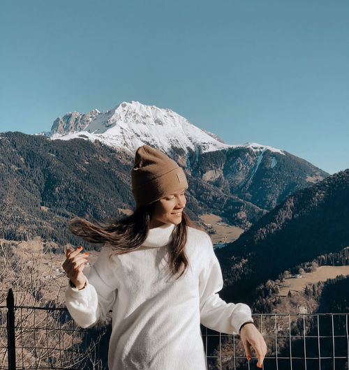 Young woman standing against snowcapped mountain and sky