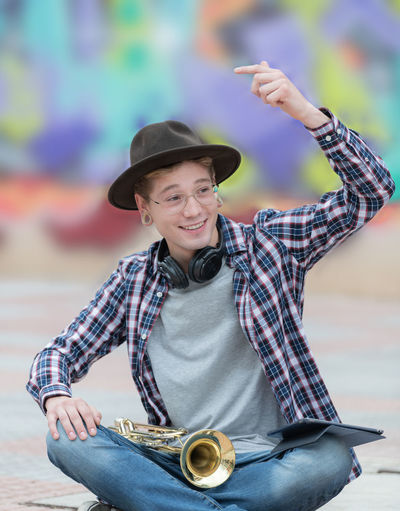 Portrait of smiling young man holding hat