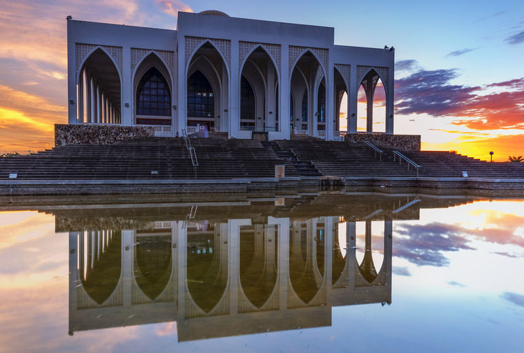 Historical building reflecting in pool during sunset
