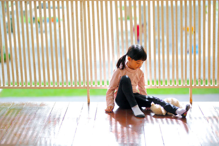 Side view of boy sitting on wooden floor
