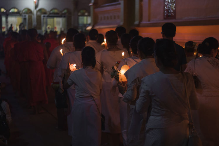 Rear view of people with lit candles walking on street during traditional festival