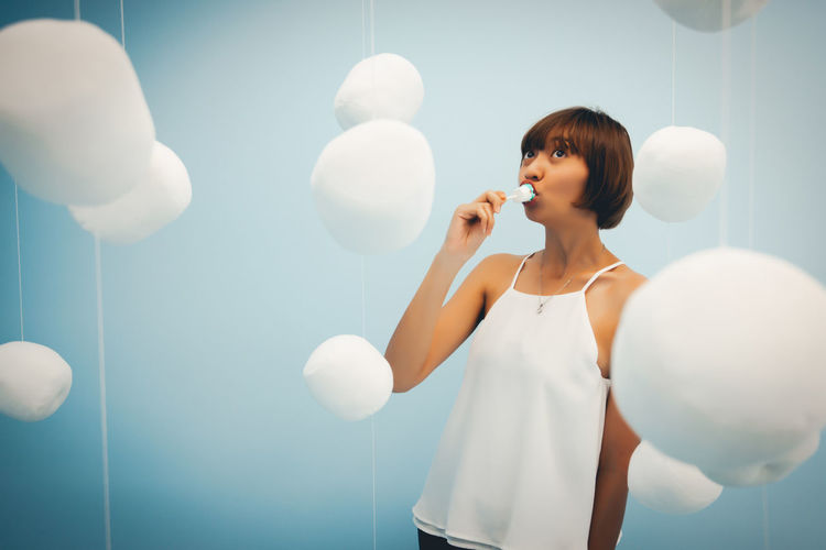 Adult Balloon Beautiful Woman Blowing Front View Hairstyle Holding Indoors  Leisure Activity Lifestyles Light Looking One Person Real People Standing Three Quarter Length Waist Up White Color Women Young Adult Young Women