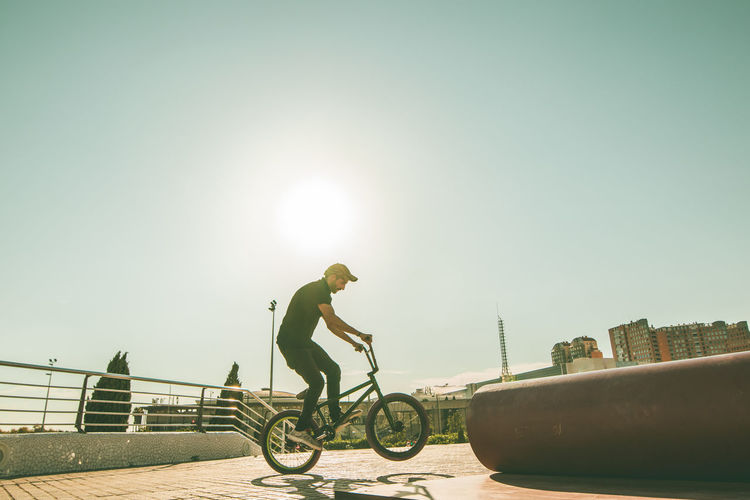Side view of man riding bicycle against sky
