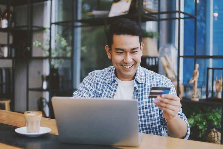 Smiling man holding credit card using laptop while sitting in cafe