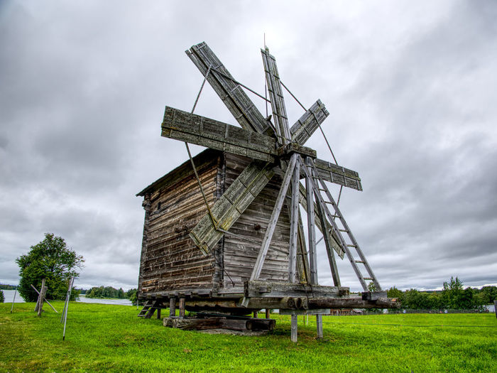 Traditional russian windmill on field against sky