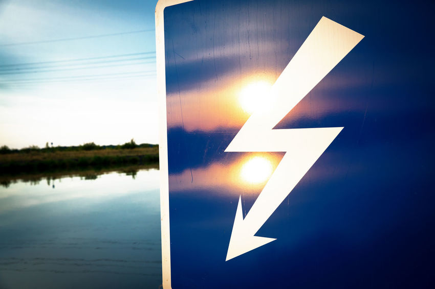 Arrow Symbol Blue Close-up Communication Danger Day Electricity  Evening Flash Glowing Guidance High Voltage Line High Voltage Sign Illuminated Lightning Nature No People Outdoors Power Line  Reflection Sign Sky Symbol Warning Sign Water