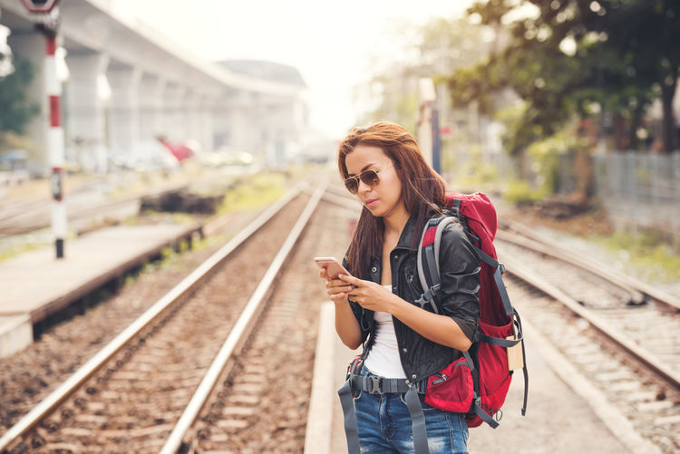 Young woman using phone while standing on railroad tracks