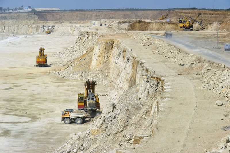 Excavator loading dumper truck on mining site