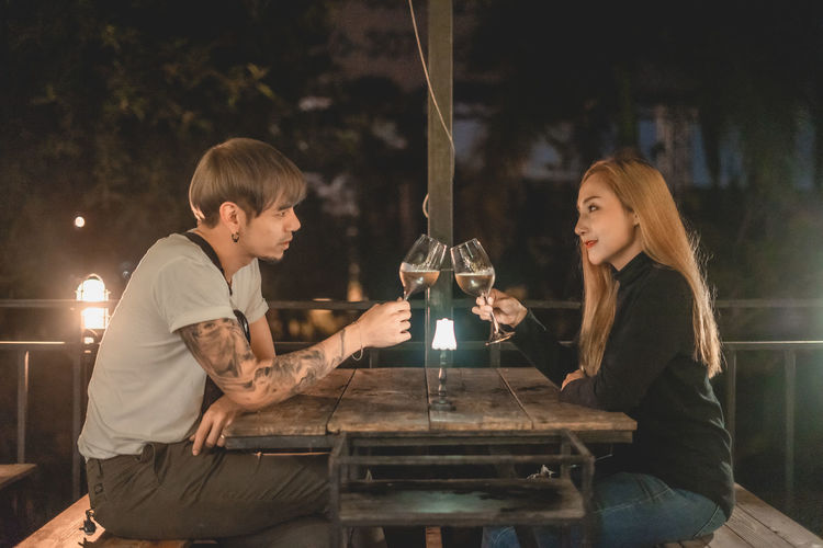 Young couple sitting on table at sidewalk cafe