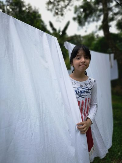 Portrait of girl standing by clothes drying on clothesline