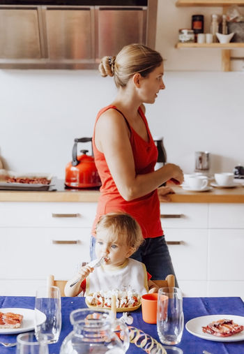 Boy Having Food By Mother Standing In Kitchen At Home
