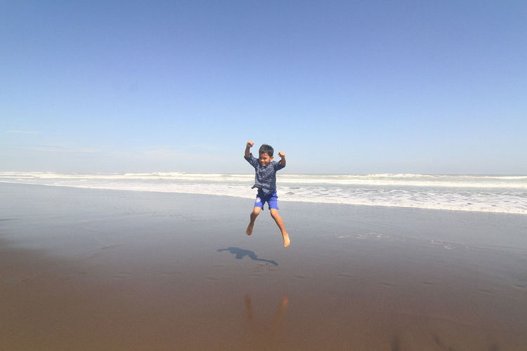 Full length of boy jumping at beach against sky