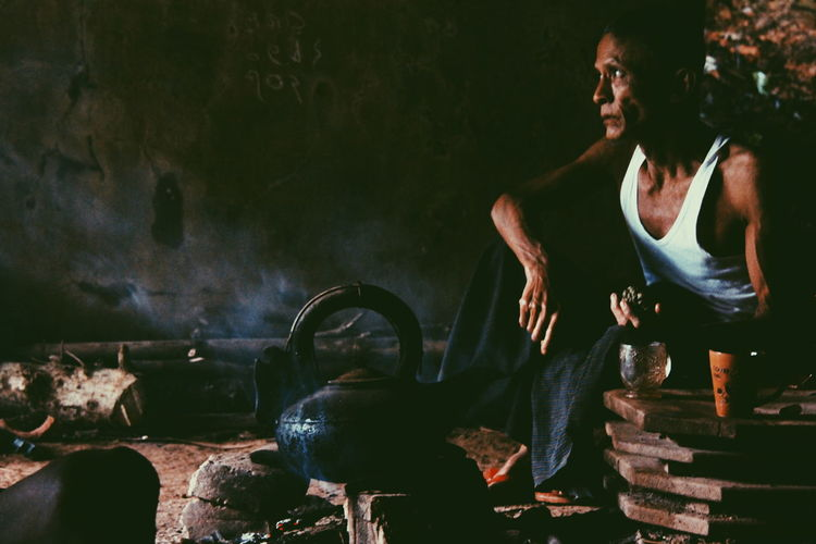 Thoughtful mature man looking away while sitting in hut