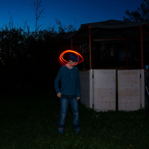 Full length of boy playing with light trails while standing on grass at night