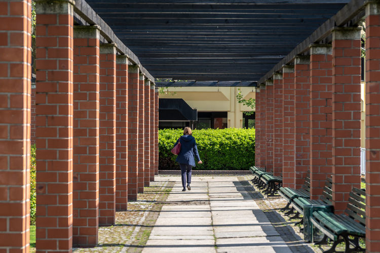 Rear View Of Woman Walking On Footpath Amidst Columns