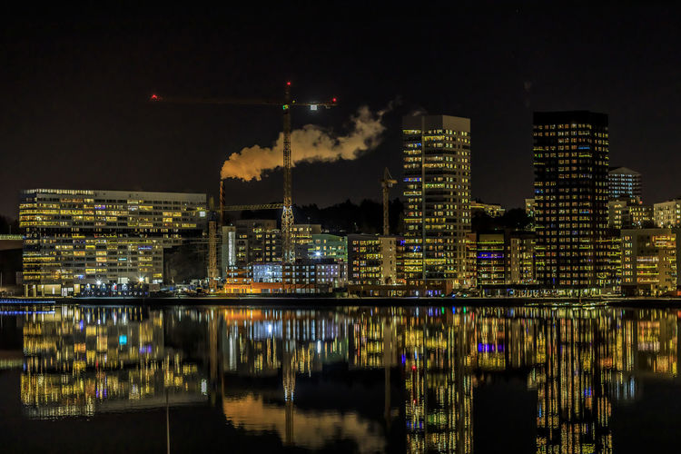 Night time skyline of a newly constructed area in the southern part of Stockholm. Building Exterior Night Architecture Illuminated Reflection Built Structure City Water Building Waterfront No People Sky River Nature Outdoors Factory Cityscape Modern Industry Pollution Skyscraper Stockholm Liljeholmen