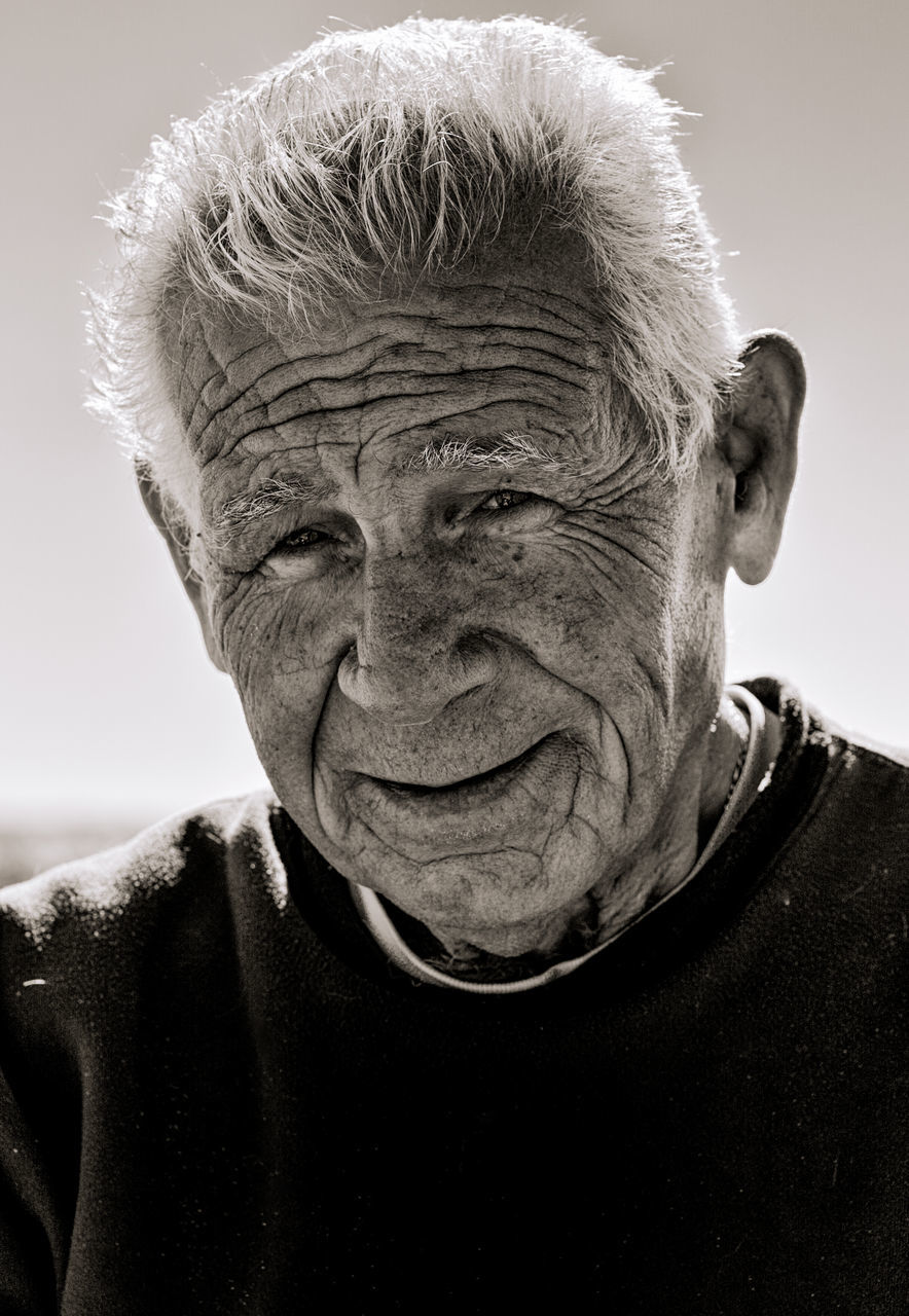 senior adult, senior men, real people, one person, wrinkled, portrait, one senior man only, headshot, looking at camera, lifestyles, close-up, human face, day, outdoors, men, people