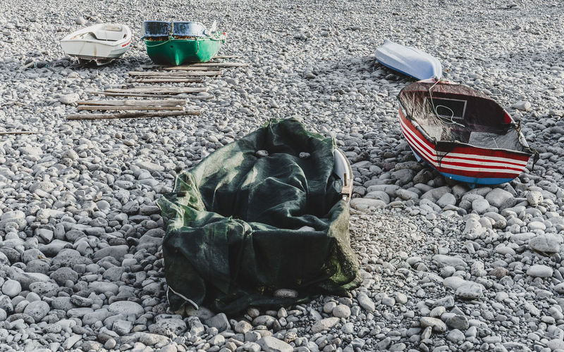 five small old fishing boats on a rocky beach Antique Abandoned Beach Boats Culture Damaged Day Fishing Boat Fishing Industry Nature No People Old Outdoors Pebble Rock Still Life Stone Traditional Transportation Vintage
