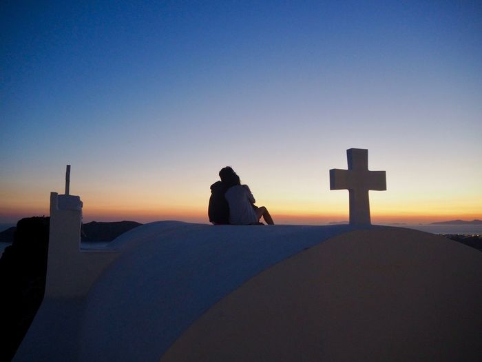 Silhouette person on cross against sky during sunset