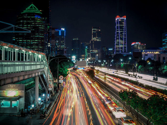 Panoramic view of illuminated city street and buildings at night