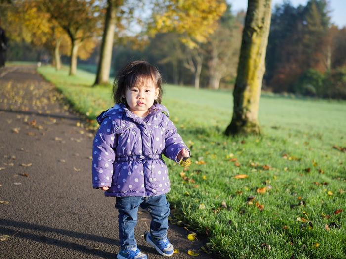 Portrait of cute baby girl standing on pathway at park