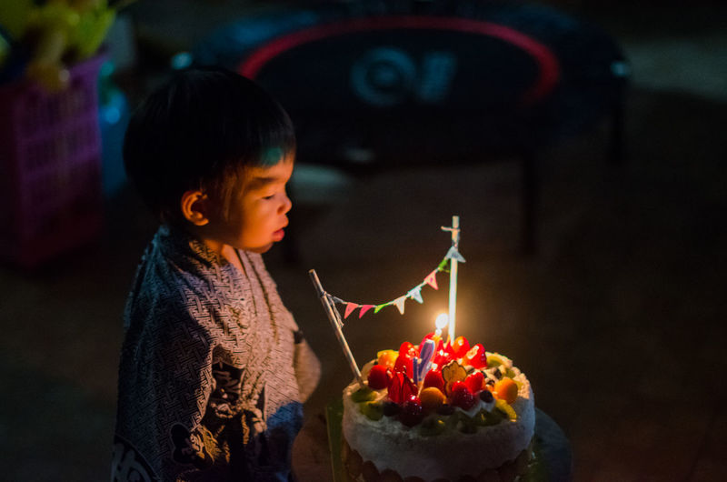 Boy looking at lit candles on cake in darkroom