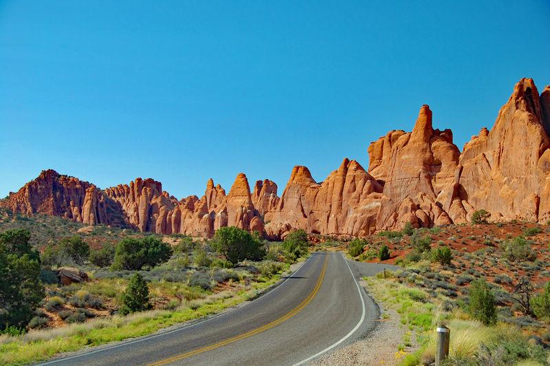 Empty road leading towards mountain against blue sky