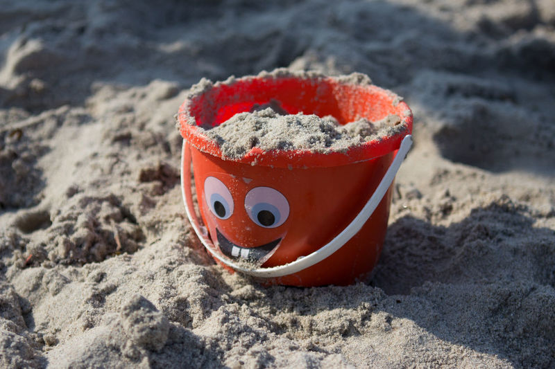 Close-Up Of Sand In Orange Bucket At Beach