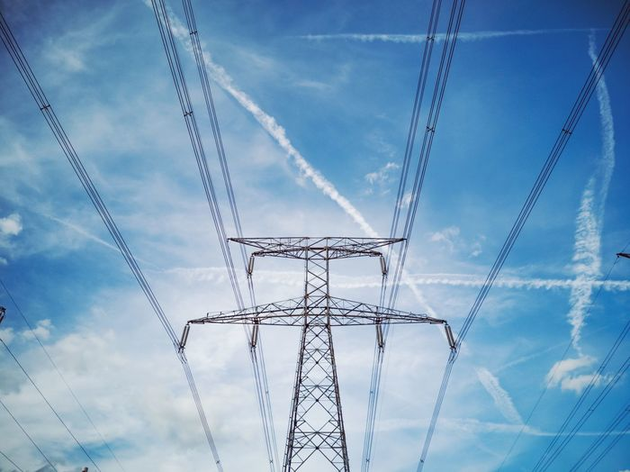 An electric pylon carrying cable, suspended in the sky they are giving us the electricity we need to power our house and devices. In the blue sky, planes left white trails looking like lines of clouds. Geometry Urban Urban Geometry Electric Wire Design Minimalism Minimal Minimalist Photography  Lookingup Looking Up High Voltage Symmetry Sky And Clouds Chemtrails Blue Sky Technology Cable Electricity  Blue Backgrounds Power Line  Sky Cloud - Sky Electricity Pylon Electricity Tower Power Supply Electric Pole Power Cable Wire Power Station