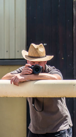 Young man wearing hat photographing with camera while standing by railing