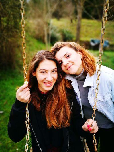Portrait of young female friends swinging on field