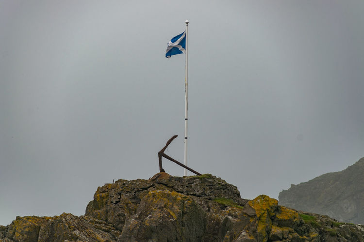 Low angle view of flag on mountain against clear sky
