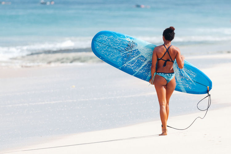 Rear View Full Length Of Woman Wearing Bikini With Surfboard At Beach
