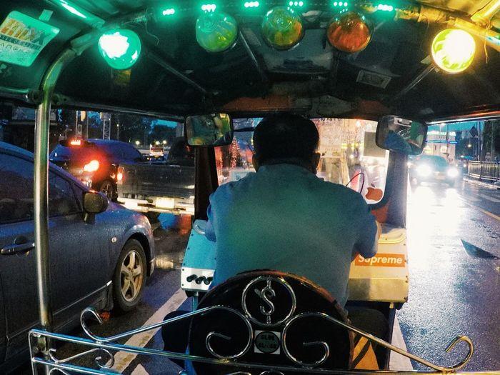 Rear view of man driving car on illuminated street at night