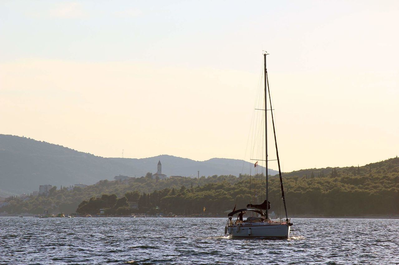 nautical vessel, transportation, mountain, water, nature, mode of transport, boat, river, beauty in nature, sunset, scenics, outdoors, waterfront, sailing, tranquility, tree, real people, sky, clear sky, mast, day, men, people