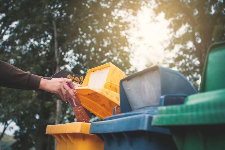 Cropped image woman throwing bottle in garbage bin