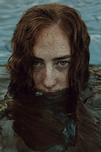 Close-Up Portrait Of Young Woman In Lake