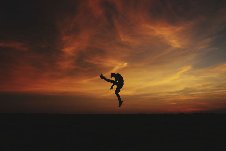 Silhouette man jumping against orange sky