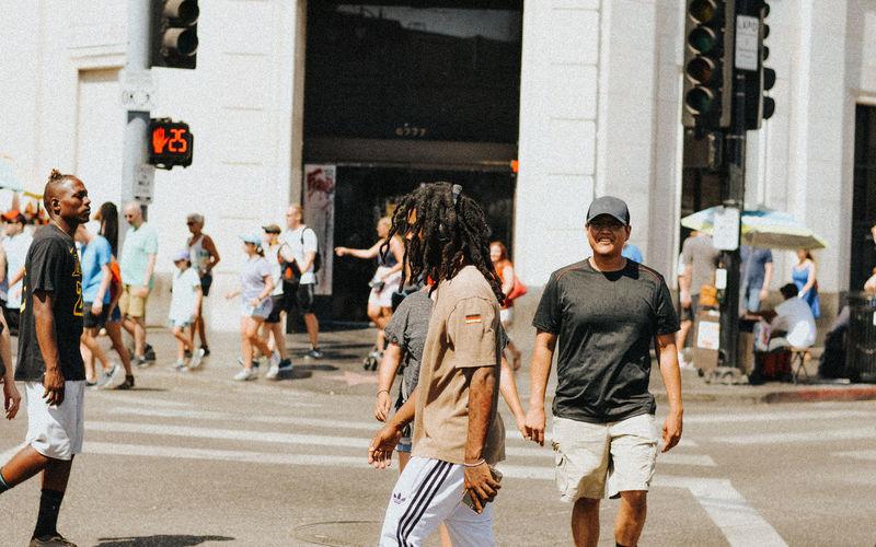 Group of people walking on road along buildings