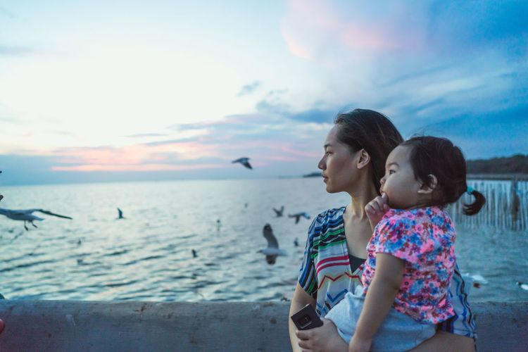 Mother carrying daughter while standing by sea against sky during sunset