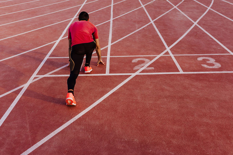 Rear view of athlete running on sports track