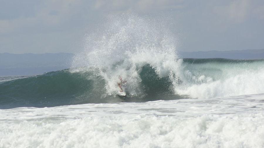 Waves splashing on sea against sky