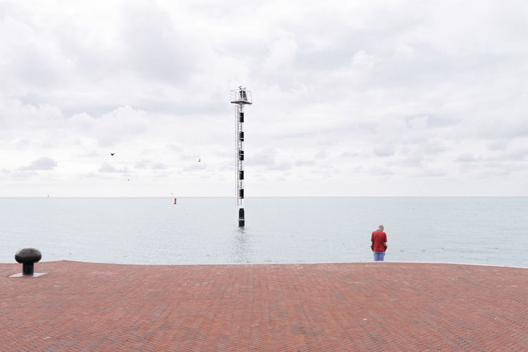 Rear View Of Person Standing Next Sea Against Cloudy Sky