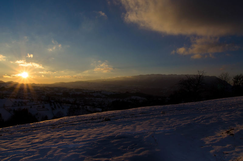 Snow covered landscape at sunset
