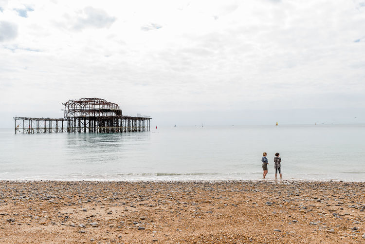 Female friends standing on shore at beach against sky in brighton