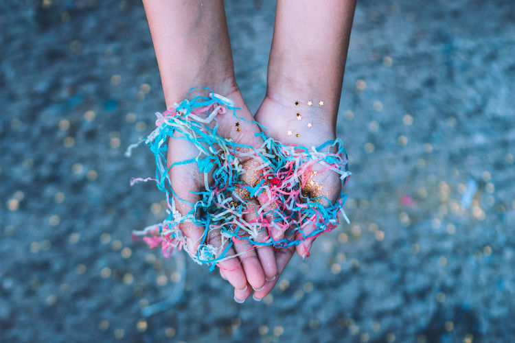Cropped Hand Of Girl Holding Colorful Confetti