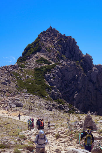 Rear view of people walking on mountain against clear sky