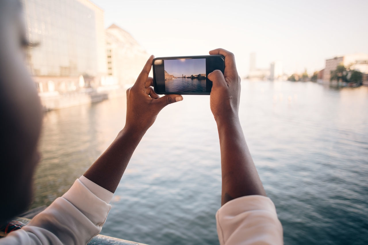 Close-up of man photographing river in city with mobile phone