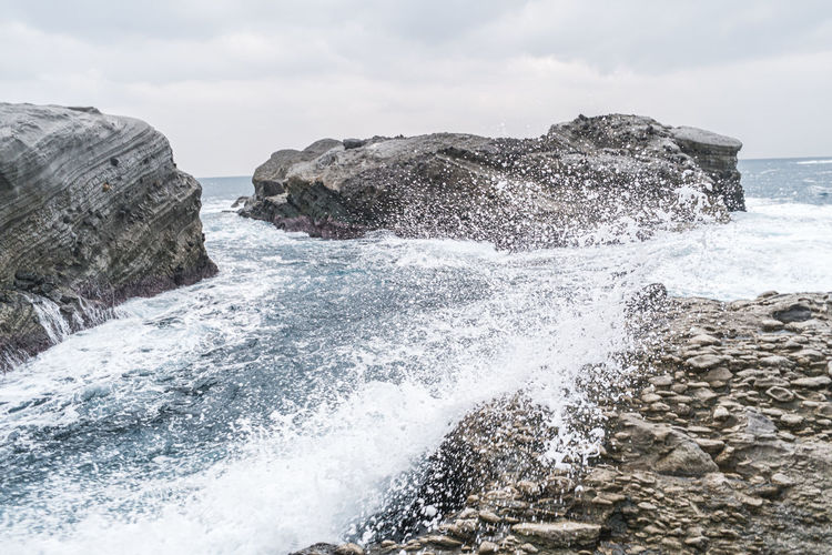 Sea waves splashing on rocks against sky