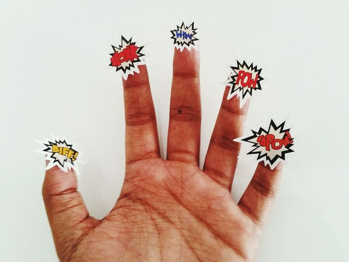 Cropped image of hand with stickers against wall